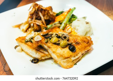 Grilled sea bass fish meat steak with vegetable in white plate