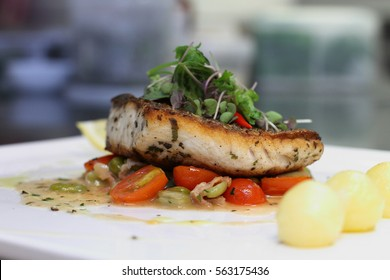 grilled sea bass with sauteed tomatoes served with potatoes ball on white plate