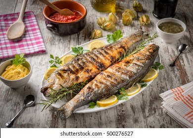 Grilled sea bass served on a plate with various sauces and decorated with parsley and lemon