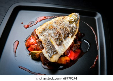 Grilled sea bream fillet on ratatouille with cherry tomato coulis