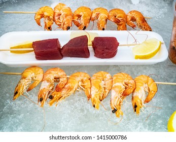 Grilled seafood. Cooled Shrimps and tuna slices with lemon on ice prepared for grilling