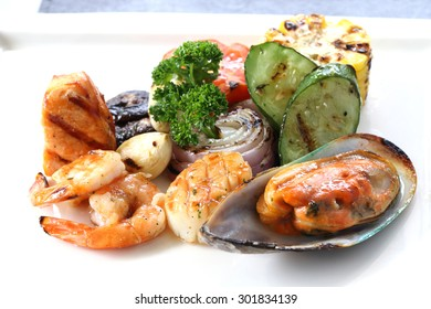 Grilled Seafood with roasted vegetables on white dish. International food