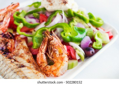 Grilled seafood with salad and feta cheese (selective focus)
