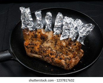 Grilled seasoned lamb rack in fry pan on black