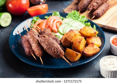 Grilled shish kebab served with fried potatoes and vegetable salad