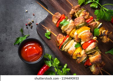 Grilled shish kebab or shashlik with vegetables  on black stone table. Pork meat. Barbeque meat dish. Top view copy space.