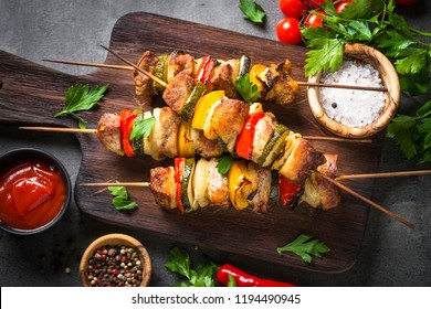 Grilled shish kebab or shashlik with vegetables  on black stone table. Pork meat. Barbeque meat dish. Top view.