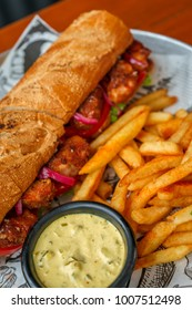 Grilled shrimp sandwich with sauce and spices, tomato, lettuce on a wooden table with French fries and white onion sauce.