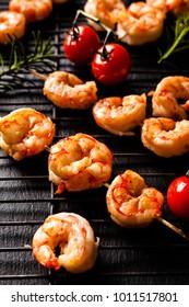 Grilled shrimp skewers. Front view. Black background.