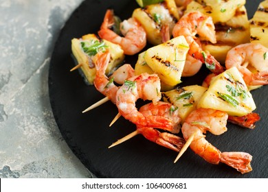 Grilled shrimp skewers with pineapple. Seafood, shellfish. Prawns skewers with herbs, pineapple, sweet chili and lime on black stone plate