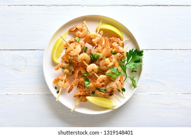 Grilled shrimp skewers. Prawns skewers with greens, spices and lemon on white plate over wooden table. Tasty seafood. Healthy snack. Top view, flat lay.