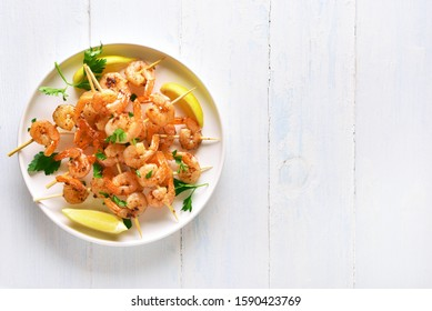 Grilled shrimp skewers. Prawns skewers with greens, spices and lemon on white plate over wooden background with free space. Tasty seafood. Healthy snack. Top view, flat lay.