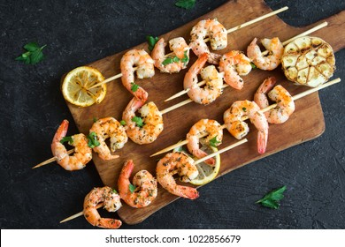 Grilled shrimp skewers. Seafood, shelfish. Shrimps Prawns skewers with herbs, garlic and lemon on black stone background, copy space. Shrimps prawns brochette kebab. Barbecue srimps prawns.