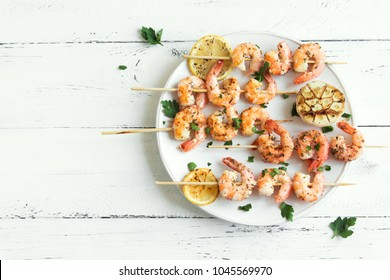 Grilled shrimp skewers. Seafood, shelfish. Shrimps Prawns skewers with spices and fresh herbs on white wooden background, copy space. Shrimps prawns brochette kebab. Barbecue srimps prawns.