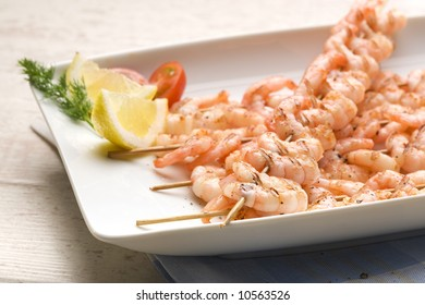 grilled shrimp spits on white plate decorated with lemon slice, pepper, tomato and dill