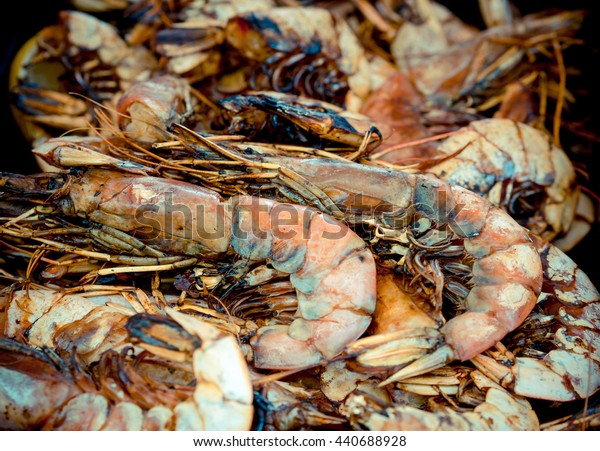Grilled shrimps closeup - food background with large roast prawns. Fresh seafood in a beach restaurant.