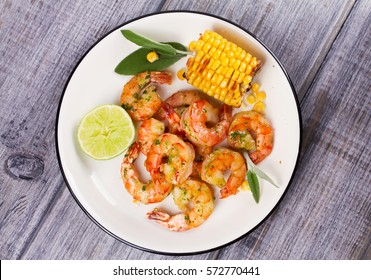Grilled shrimps and corn garnished with lime and sage leaves. Prawns on white plate. View from above, top studio shot