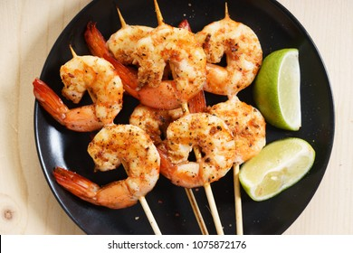 Grilled shrimps on skewer with lime slices and salad
