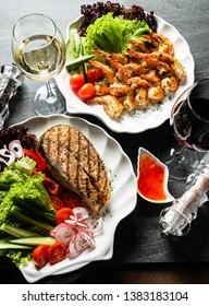 grilled shrimps and salmon steak with fresh vegetables and wine