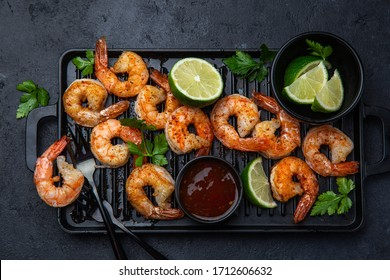 grilled shrimps with sweet chilli sauce and lime , black background, top view