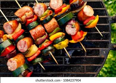 Grilled skewers of meat, sausages and various vegetables on a grill plate, outdoors, top view. Grilled food, bbq
