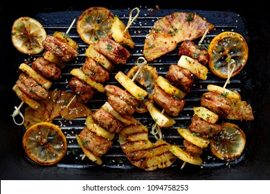 Grilled skewers with pineapple  and chicken meat  with herbs on a grill plate. Fruit and meat skewers, top view