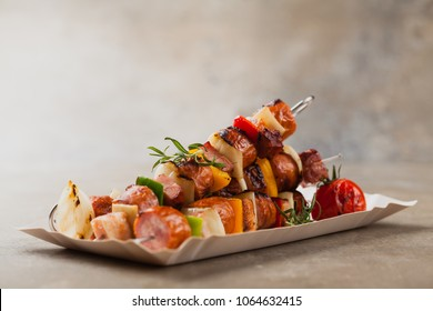 Grilled skewers with sausage, bacon and vegetables. Front view. stone background.