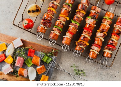 Grilled skewers with sausage, bacon and vegetables. Top view. stone background.