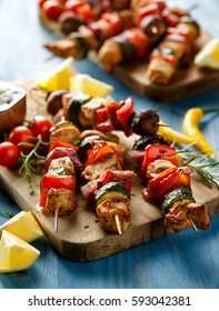 Grilled skewers with vegetables and meat on a blue wooden table