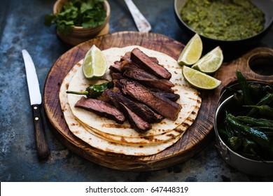 Grilled Skirt Steak Fajitas Recipe. Beef steak fajitas tacos hot tortillas with avocado salsa and green peppers.
