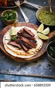 Grilled Skirt Steak Fajitas Recipe. Beef steak fajitas tacos hot tortillas with avocado salsa, herbs, lime, pepper sliced.