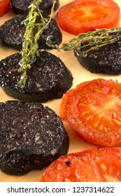 grilled slice black pudding and tomato with thyme served on a wooden board