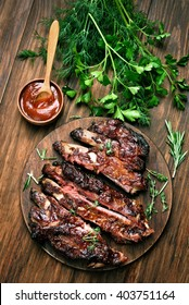 Grilled sliced barbecue pork ribs on wooden background. Top view, flat lay
