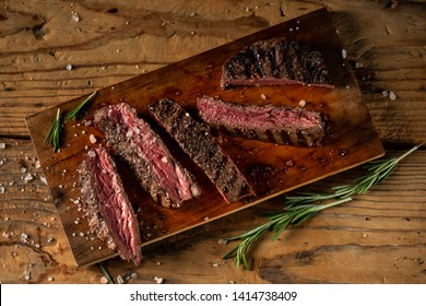 Grilled and sliced beef steak from marbled meat served on wooden board in rustic style on old wood background. Top view, flat lay photo.