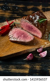 Grilled and sliced beef steak from marbled meat served on wooden board in rustic style on old wood background.