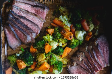 Grilled sliced beef steak on a plate with vegetables