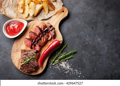 Grilled sliced beef steak on cutting board over stone table. Top view with copy space