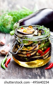 Grilled  sliced eggplant with chili in glass jar on rustic table.