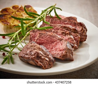 grilled sliced steak and rosemary on white plate