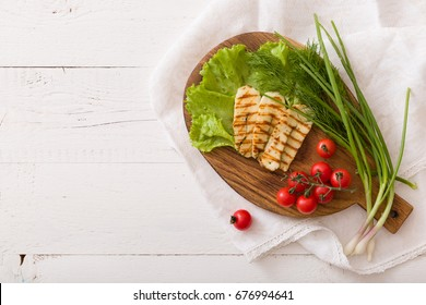 Grilled slices of homemade halloumi cheese with green salad, fresh herbs and organic tomatoes. Fried halloumi cheese with grill marks on white wooden background, top view