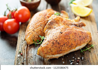 Grilled or smoked chicken breast with bone and skin on a cutting board