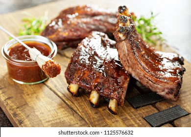 Grilled and smoked ribs with barbeque sauce on a carving board