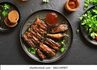 Grilled spare ribs on plate over black stone background. Top view, flat lay