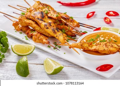 grilled spicy Chicken satay on skewers on a white rectangular plate with peanut sauce. red chili peppers, lime slices and parsley on table, view from above, close up