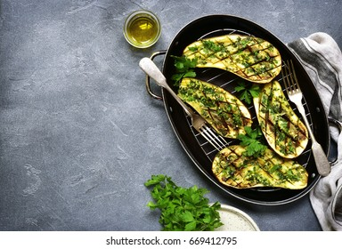 Grilled spicy eggplants on a black metal tray on dark slate,stone or concrete background.Top view.