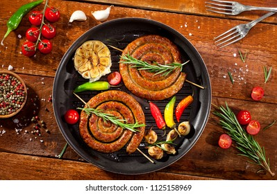 Grilled spiral sausages with vegetables and spices in a pan on wooden background