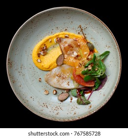 Grilled squid appetizer with orange slices and pumpkin mash isolated on black background