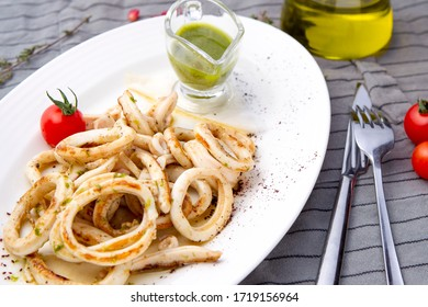 Grilled squid with basil sauce served in a white plate.