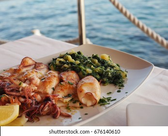Grilled squid with boiled potatoes and chard (blitva) on white plate with sea on background. Traditional Croatian food. Rovinj, July 2017.