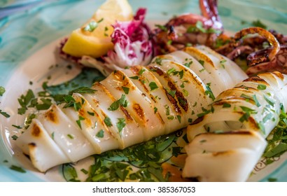 Grilled squid with lemon and vegetables  at Italian restaurant. Selective focus.